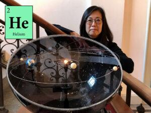 """Das Foto zeigt Prof. Dr. Sasaki auf einer Treppe im Gebäude der Sternwarte stehend. Vor ihr ist ein Modell aufgestellt, das die inneren Planeten und das Sonnensystem zeigt. Links im Bild ist in einem grünen Kasten """"He"""" zu lesen, die Abkürzung im Periodensystem für Helium."""